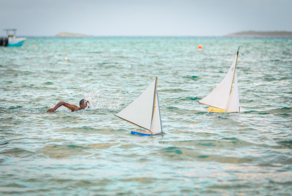 local guy swimming with Handmade sail boats